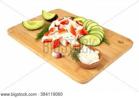 Crab Sticks Cut Meat And Vegetables Avocado Cut Cucumbers On Wooden Cutting Board Isolated On White