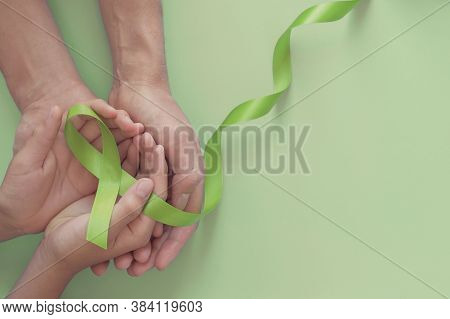 Adult And Child Hands Holding Lime Green Ribbon On Green Background, Children Mental Health Awarenes