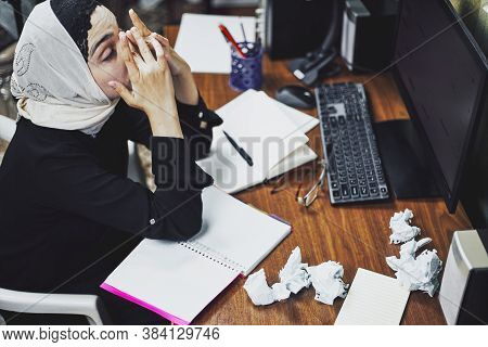 Middle Eastern Female Entrepreneur Feeling Unhappy. Busy Arabian Businesswoman Sitting Around The He