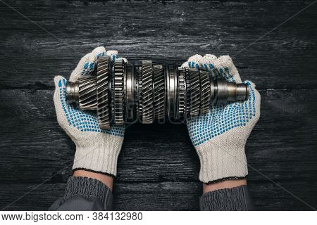 Output Shaft Of Car Gearbox In Car Service Worker Hands On Black Background.
