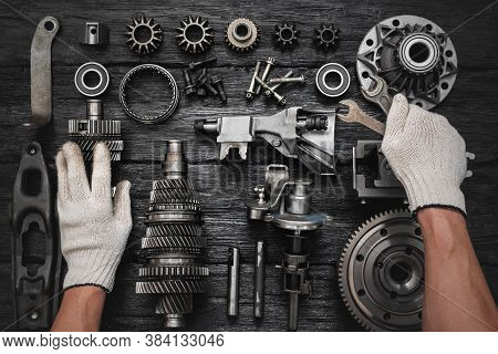 Car Gearbox Spare Parts And Car Service Worker Hands With Wrenches On The Black Flat Lay Background.