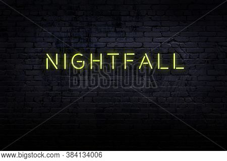 Neon Sign With Inscription Nightfall Against Brick Wall. Night View