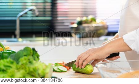 Young Asian Woman Is Preparing Healthy Food Vegetable Salad By Cutting Cucumber For Ingredients On C