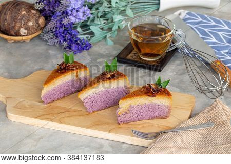 Piece Of Taro Chiffon Cake Topped With Thai Taro Custard And Fried Onion On Wooden Board With Tea, C