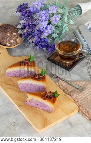 Piece Of Taro Chiffon Cake Topped With Thai Taro Custard And Fried Onion On Wooden Board With Tea, T