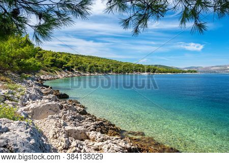 Rocky shore with turquoise sea water. Adriatic coast, tourist destination in Croatia. Idyllic summer seascape with crystal clear sea water