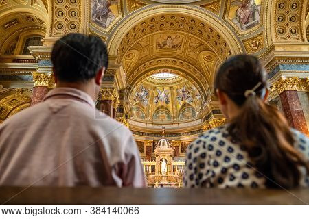 Budapest, Hungary - August 25, 2019: Unidentified people praying inside St. Stephen's Basilica in Budapest
