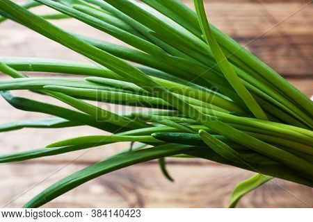Green Onions Or Shallots On A Wooden Background With Copy Space.