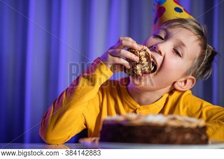 Happy child takes a piece of celebration cake and then bite it.  Cute boy eats cake on his birthday. Happy boy with cone on head celebrates his birthday. Caucasian child and birthday cake