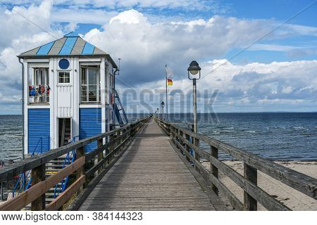 Lifeguard Station House At The Sea-bridge Of Lubmin Under A Blue Sky With Clouds, Seaside Tourist Re