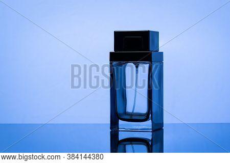 Black Perfume Bottle On A Blue Background. Mockup Of Black Perfume Bottle