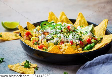 Mexican Street Corn Salad With Cheese And Nachos Chips In A Black Platter. Mexican Food Concept.