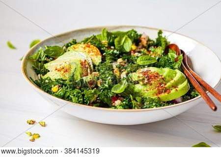 Healthy Salad With Kale, Quinoa, Nuts And Avocado In A White Bowl. Healthy Vegan Food Concept.