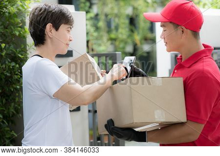 Asian Delivery Man In Red Uniform Delivering Parcel Box To Woman Recipient At Home With Recipient Si
