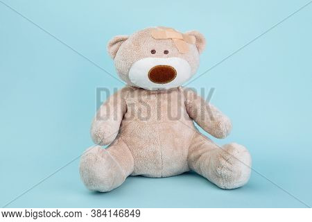 Stuffed Bear Animal As A Symbol Of Children Healtcare Concept Isolated On Blue Background