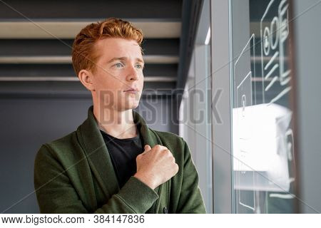 Young serious software developer keeping hand on chest while standing in front of noticeboard and looking at sketches of mobile application