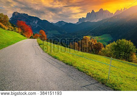 Wonderful Autumn Alpine Scenery With Colorful Deciduous Trees On The Slopes At Sunrise, Funes Valley