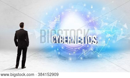 Rear view of a businessman standing in front of CYBERNETICS inscription, modern technology concept