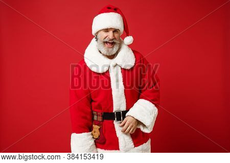 Funny Elderly Gray-haired Mustache Bearded Santa Man In Christmas Hat Posing Isolated On Red Backgro