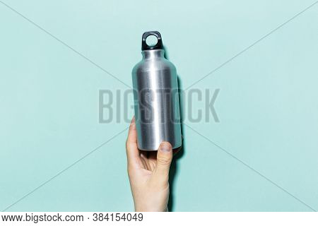 Close-up Of Male Hand, Holding Aluminum, Thermo Water Bottle On The Background Of Cyan Color.