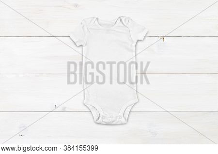 Top Down View Of A White Onesie On A Modern White Wood Background. Plenty Of Space To Add Your Own D