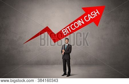 Young business person in casual holding road sign with BITCOIN CASH inscription, business direction concept