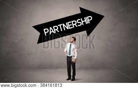Young business person in casual holding road sign with PARTNERSHIP inscription, business direction concept