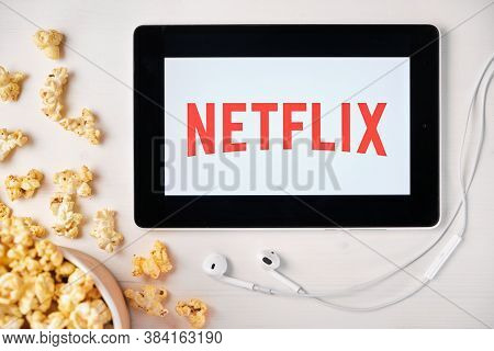 Netflix Logo On The Screen Of The Tablet Laying On The White Table And Sprinkled Popcorn On It. Appl