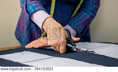 Detail Of Hands Of Dressmaker Cutting A Cloth To Make A Garment