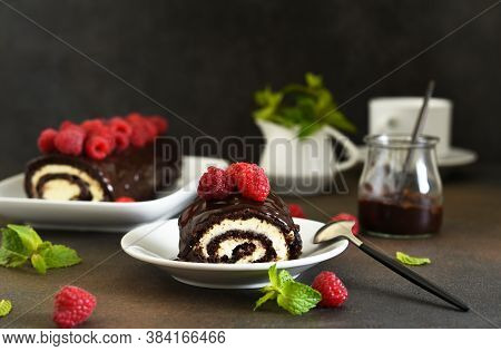 Chocolate Roll With Cream Cheese And Raspberries, With A Cup Of Coffee On A Dark Background.