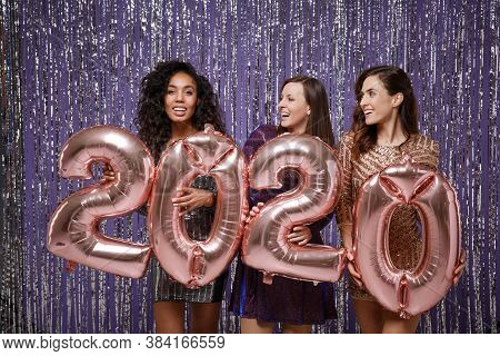 Women In Fancy Sparkling Dresses Posing Isolated Over Vibrant Purple Violet Silver Background. Posit