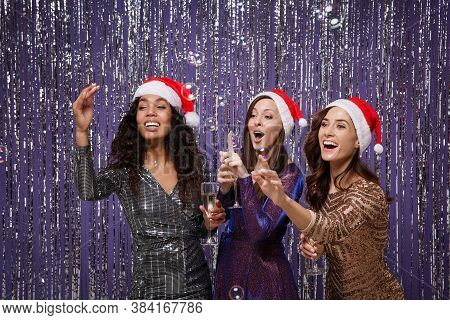 Three Women In Fancy Sparkling Dresses Posing Isolated Over Vibrant Purple Silver Background. Positi