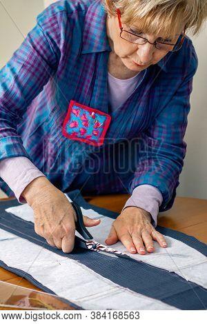Dressmaker Cutting A Cloth To Make A Garment In Her Workshop