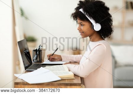 Happy Black Teen Girl At Laptop Doing Homework Online Sitting At Table At Home. Distant Education, R