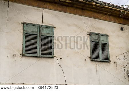 Facade Of An Abandoned Building With Old Windows With Green Shutters. Plastered Weathered Wall