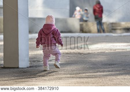 Toddler Runs To The Children. Little Girl Walking On The Street. Concrete Jungle And Children.