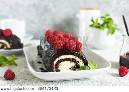 Biscuit Roll With Chocolate And Raspberries On A Light Concrete Background.
