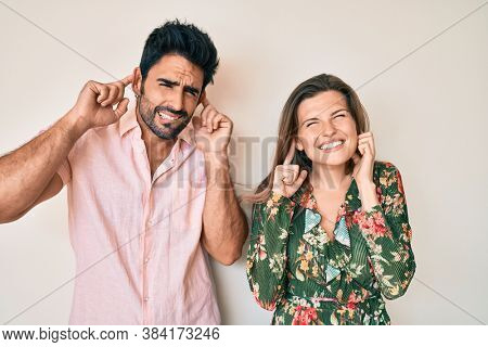 Beautiful young couple of boyfriend and girlfriend together covering ears with fingers with annoyed expression for the noise of loud music. deaf concept.