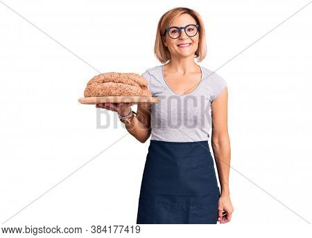 Young blonde woman holding wholemeal bread looking positive and happy standing and smiling with a confident smile showing teeth