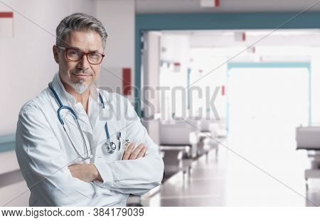 Smiling doctor in glasses on hospital corridor, Trustworthy older man with gray hair.
