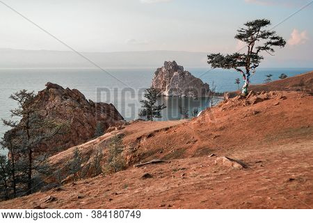 Cape Shamanka Rock In Lake Baikal Among The Grassy Steppes With Coniferous Larch Trees, Against The