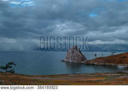 Cape Shamanka Rock In Lake Baikal Among The Grassy Steppes, Against The Background Of Mountains And