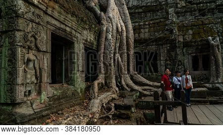 Siem Reap, Cambodia - December, 30, 2019 : Family Takes Photo At Famous Tree At Ta Prohm Temple Near
