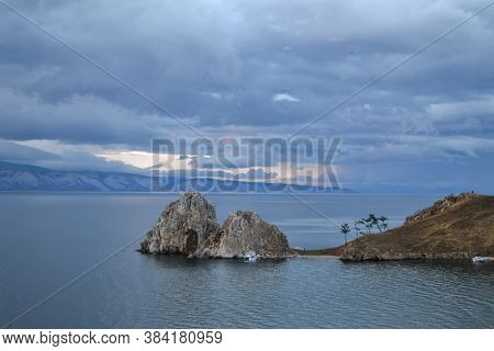Cape Shamanka Rock In Clear Lake Baikal Among Mountains And Clouds, Blue Landscape