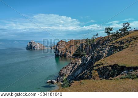 Cape Shamanka In Clear Blue Lake Baikal Among The Grassy Steppes With Coniferous Larch Trees, Rocks,