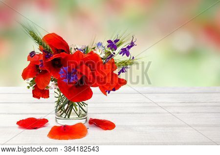 Red Poppies, Cornflowers, Ears Of Green Wheat, Chamomile In Small Vase On White Wooden Table On Summ