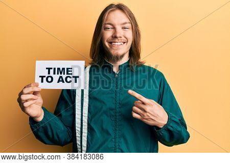 Handsome caucasian man with long hair holding time to act banner smiling happy pointing with hand and finger