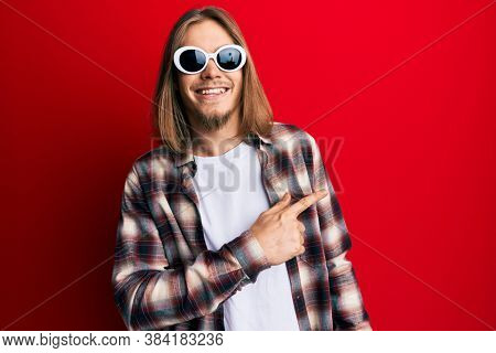 Handsome caucasian man with long hair wearing hipster shirt wearing sunglasses smiling cheerful pointing with hand and finger up to the side