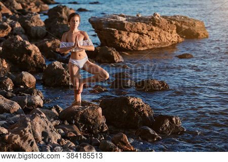 Woman Balancing On One Leg. Yoga Time, Solitude, Meditation And Contemplation Concept. Seascape View