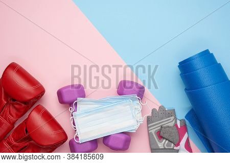 Pair Of Red Leather Boxing Gloves, A Blue Neoprene Mat, A Medical Face Mask And A Pair Of Dumbbells.